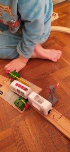 Un enfant dont on ne voit que les jambes et un bras joue avec un circuit de train en bois assis sur un parquet